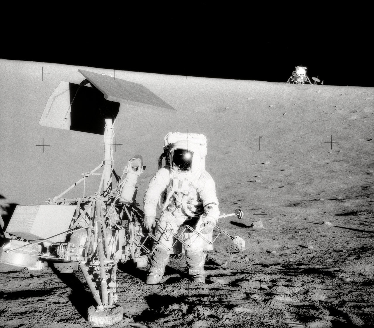 Astronaut and robotic spacecraft on the Moon.