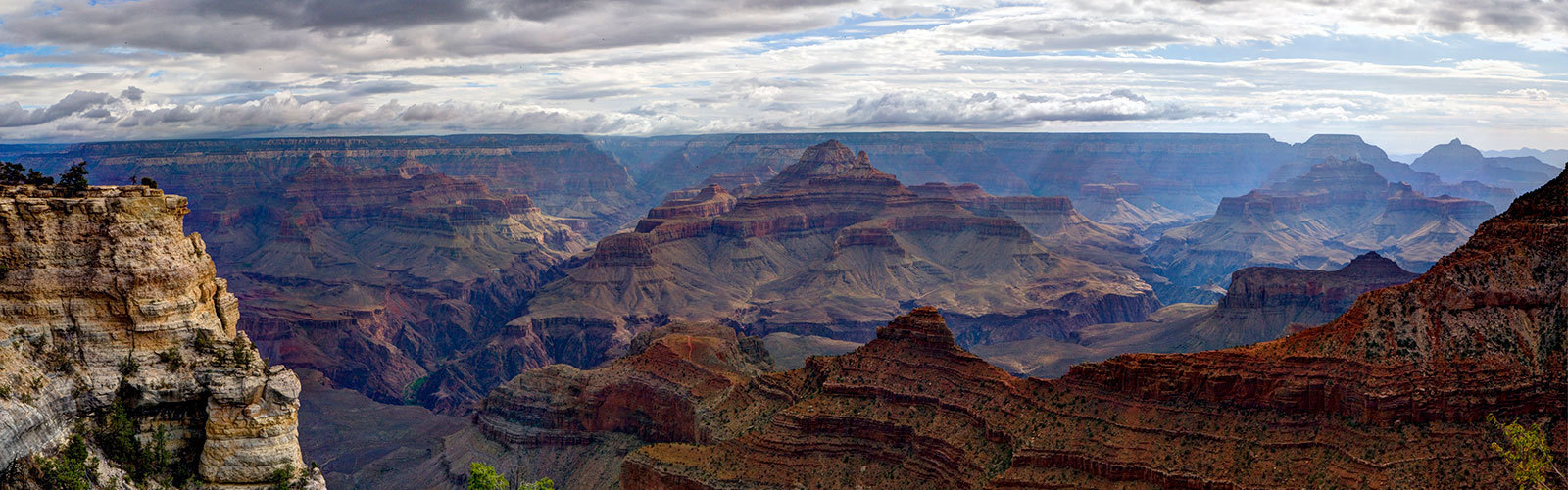 View of sprawling Grand Canyon showing many hues of red rock and against a blue sky.