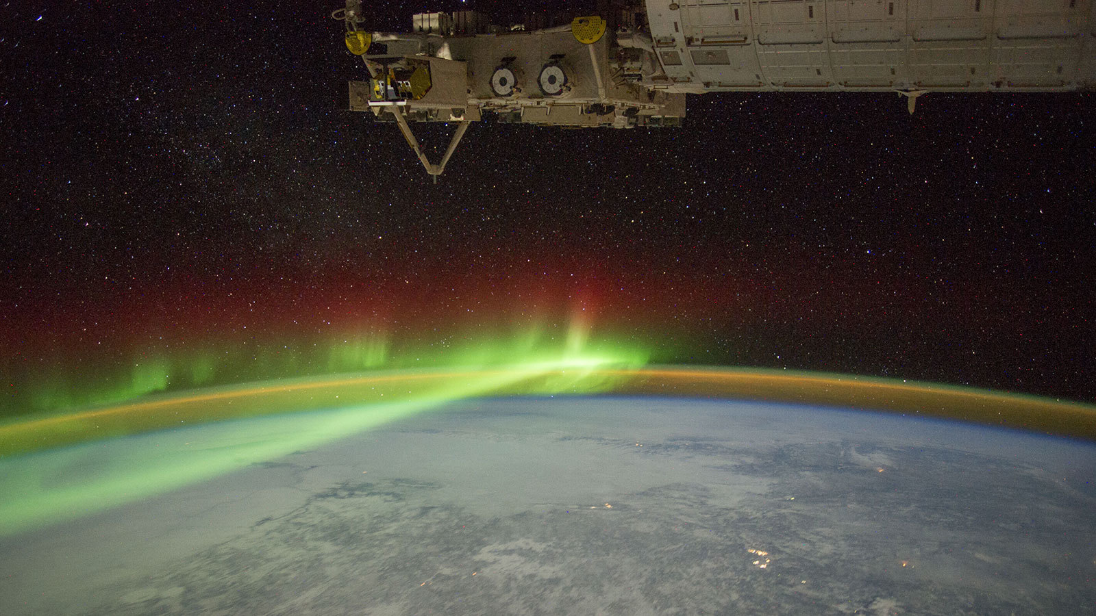 The limb of Earth with glowing auroras and a thin band of atmosphere under part of the International Space Station.