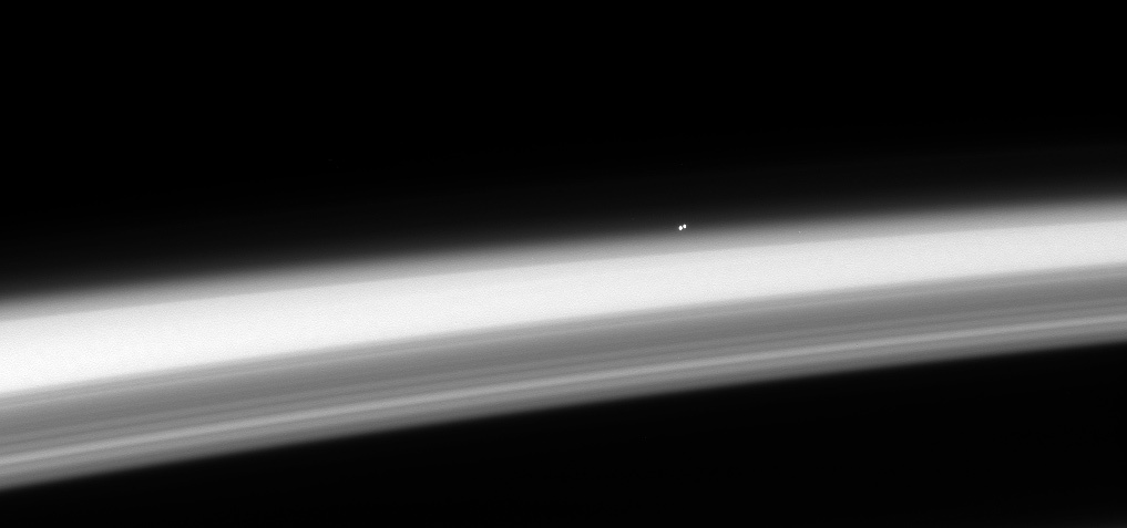 The trinary star Alpha Centauri, hangs above the horizon of Saturn
