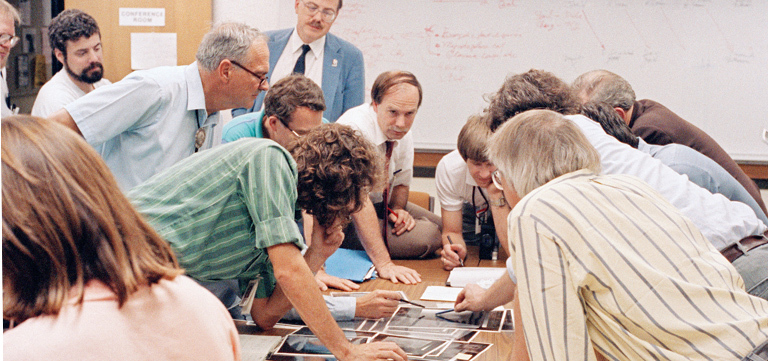 Members of the Voyager science team pore over fresh images of Neptune's moon Triton as data from Voyager 2 stream into JPL in August 1989. Image Credit: NASA/JPL-Caltech