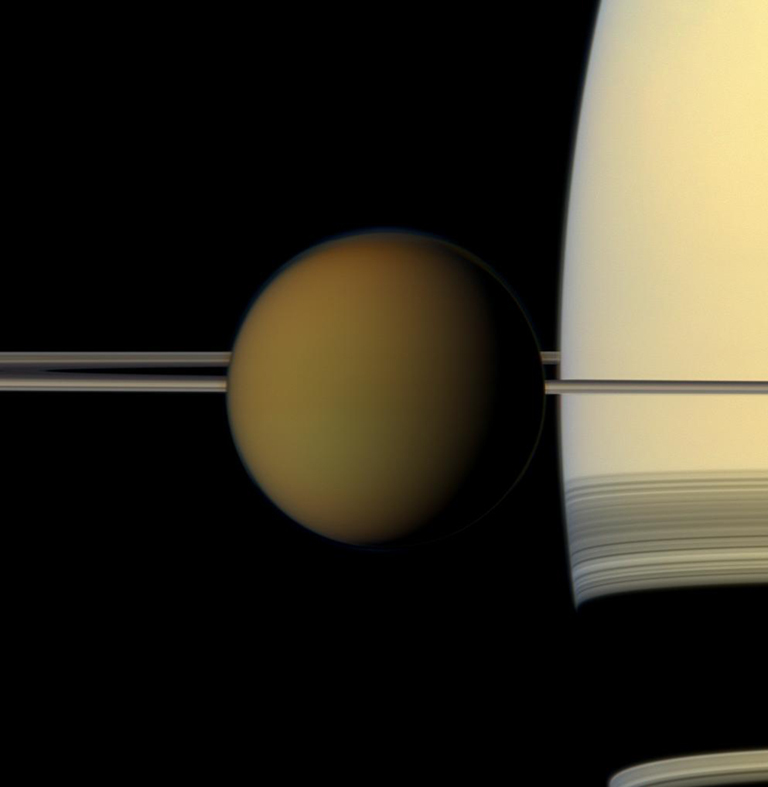 The colorful globe of Saturn's largest moon, Titan, passes in front of the planet and its rings in this true color snapshot from NASA's Cassini spacecraft. The combined images were obtained on May 21, 2011.