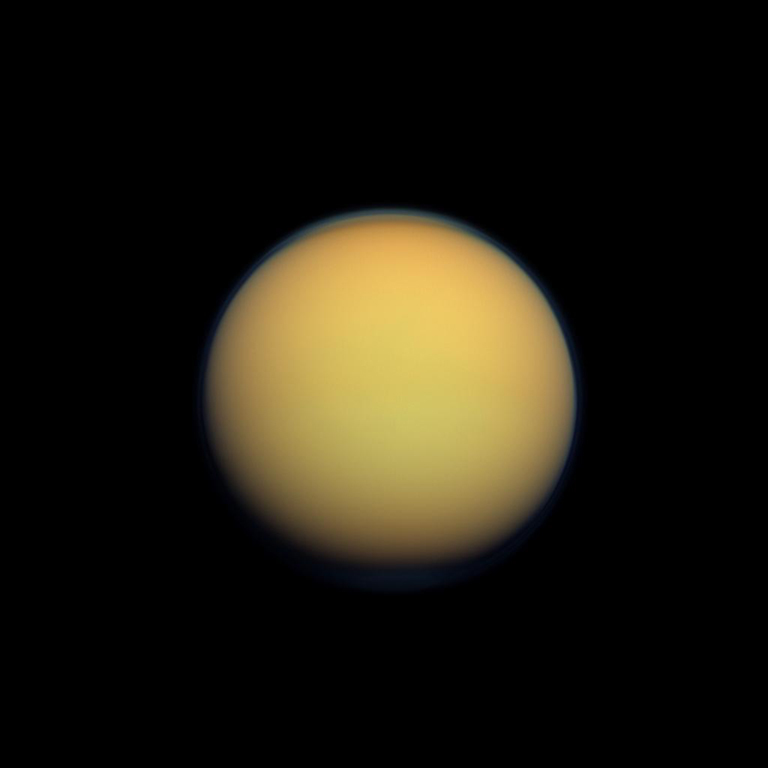 Titan's atmosphere makes Saturn's largest moon look like a fuzzy orange ball in this natural color view from the Cassini spacecraft.