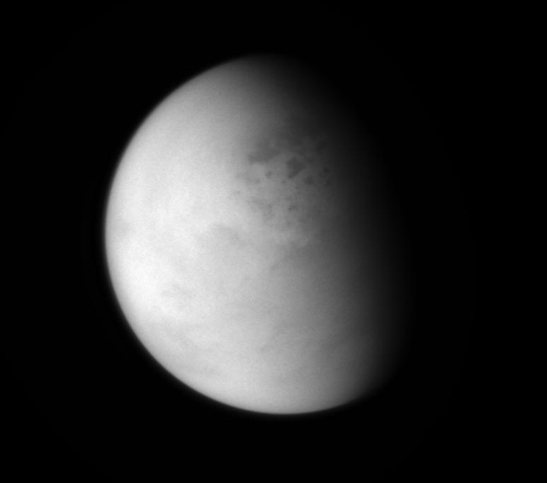 The Cassini spacecraft peers down through layers of haze to glimpse the lakes of Titan's northern regions. This image was released on April 7, 2014.