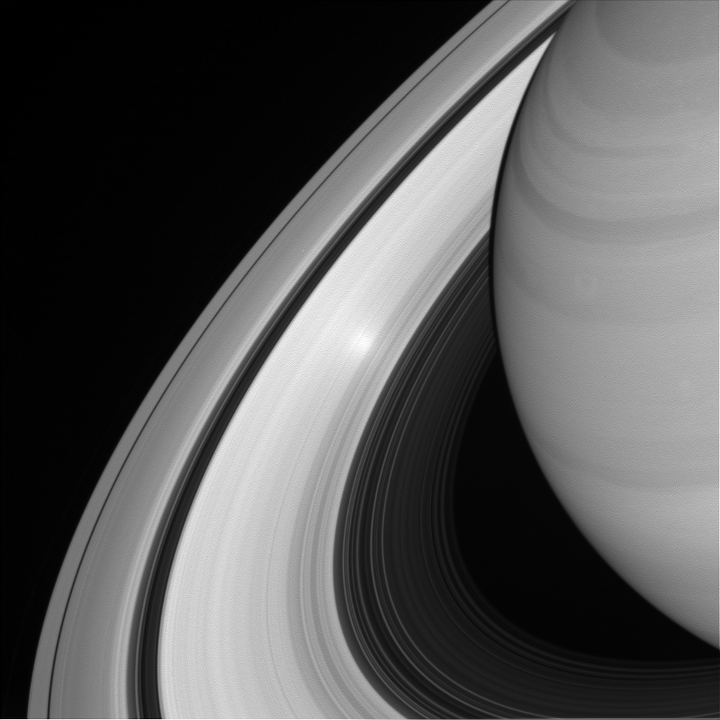 Black and white of Saturn and rings with an extra bright spot on them.
