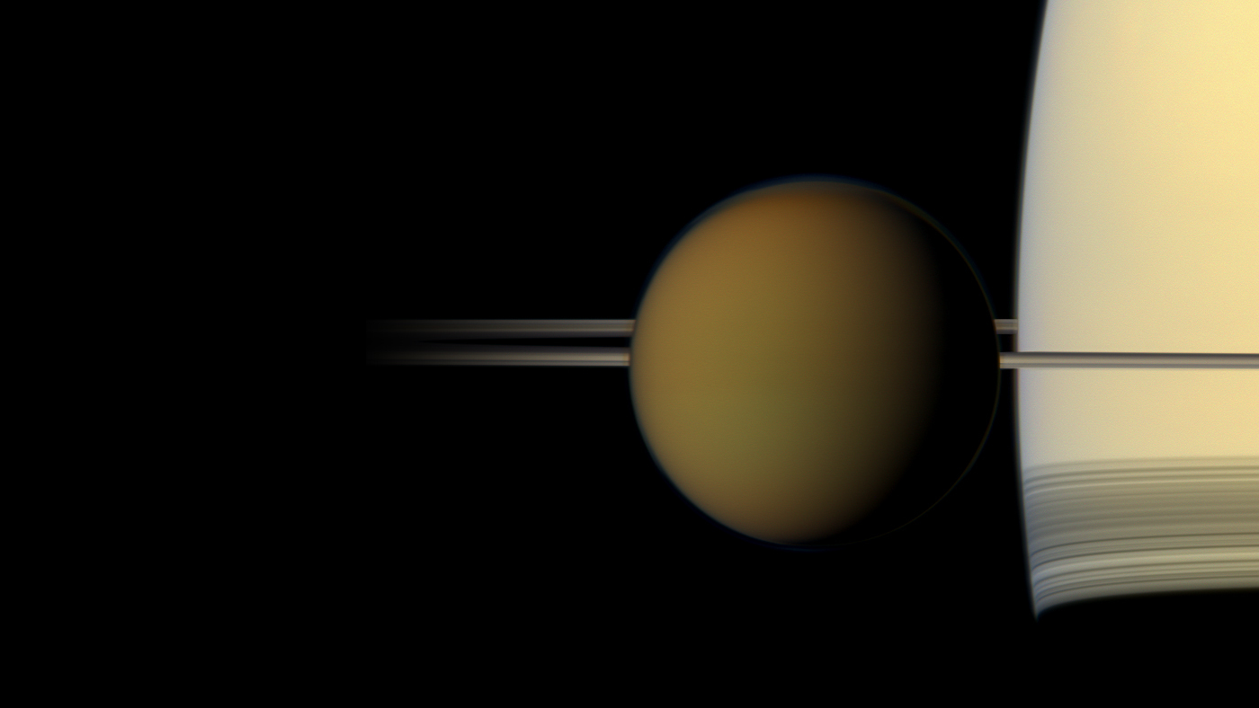 A color image of the hazy globe of Titan as it hangs in front of Saturn and its rings
