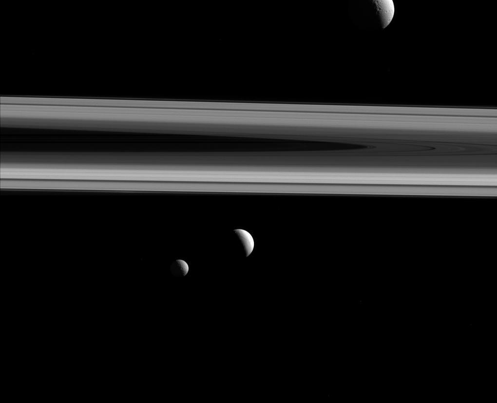 Black and white image of three moons and Saturn's rings.