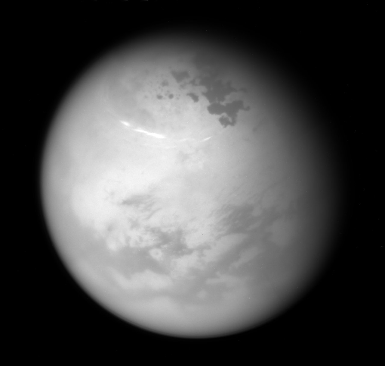 NASA's Cassini spacecraft sees bright methane clouds drifting in the summer skies of Saturn's moon Titan, along with dark hydrocarbon lakes and seas clustered around the north pole. › Full image and caption