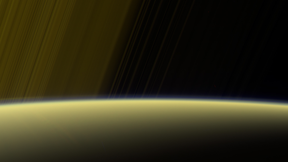 Enhanced color view showing a yellowish Saturn with rings above it.