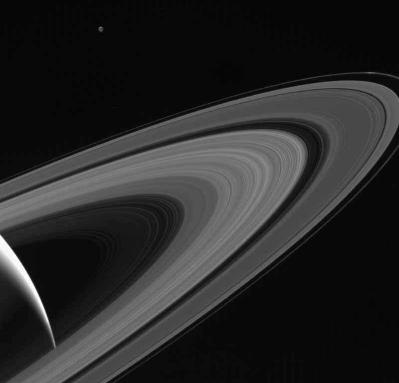 Cassini gazes across the icy rings of Saturn toward the icy moon Tethys, whose night side is illuminated by Saturnshine, or sunlight reflected by the planet. › Full image and caption
