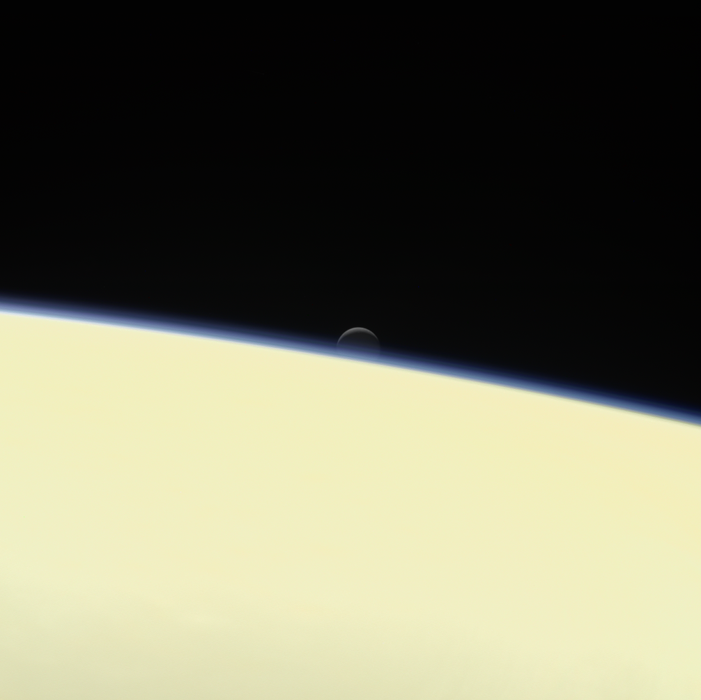 Saturn's active, ocean-bearing moon Enceladus sinks behind the giant planet in a farewell portrait from NASA's Cassini spacecraft. This view of Enceladus was taken by NASA's Cassini spacecraft on Sept. 13, 2017. It is among the last images Cassini sent back.