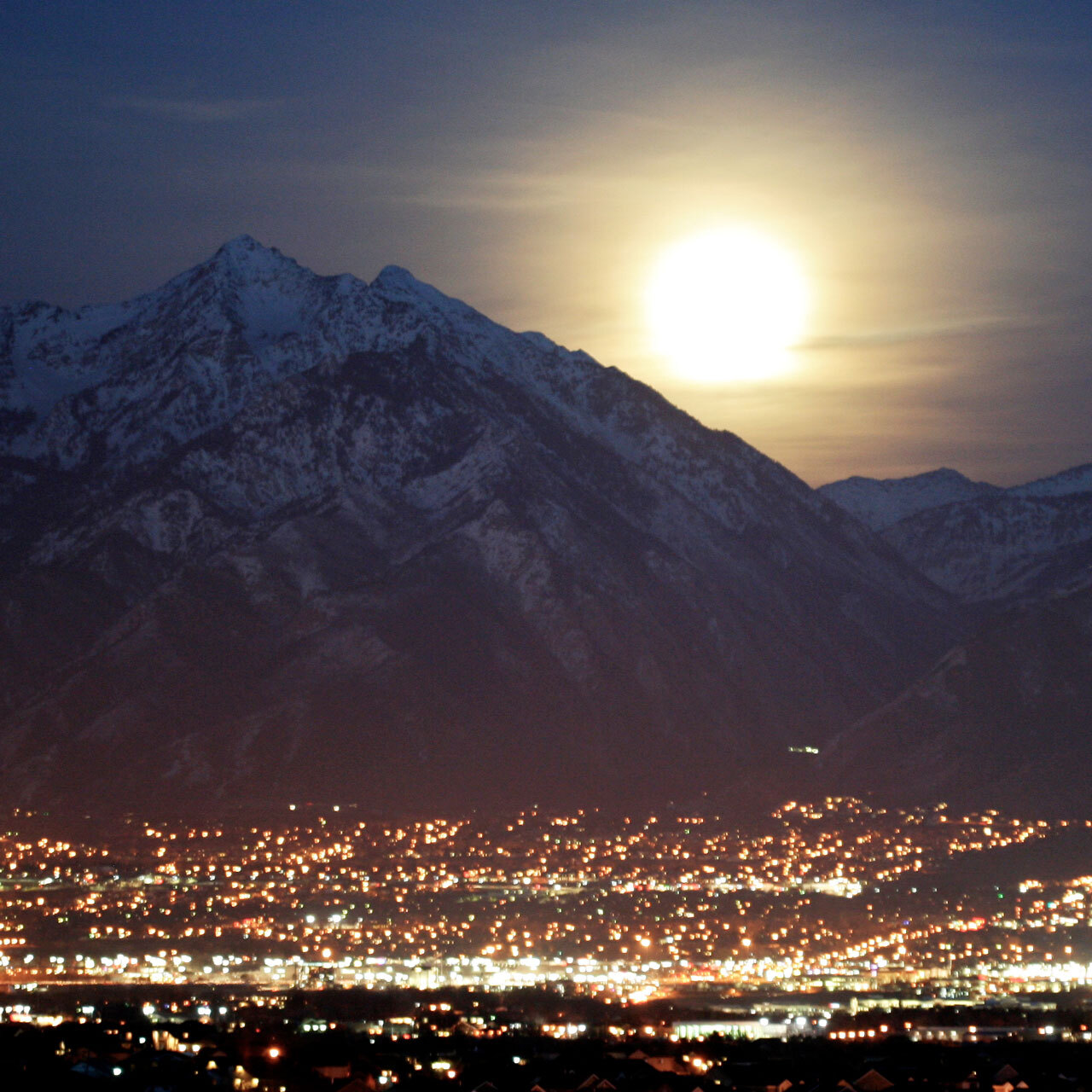 Bright moon rising over mountains with city lights in the foreground.