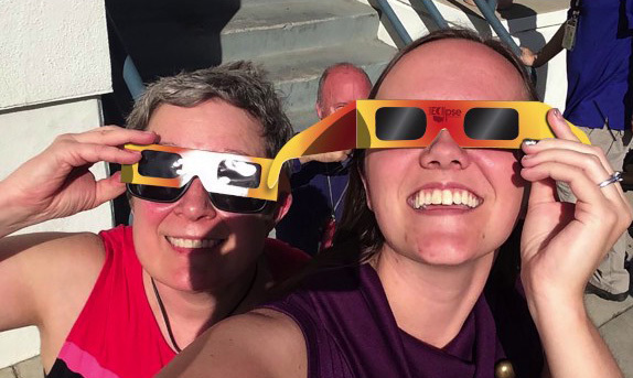 Two smiling women wearing eclipse glasses.