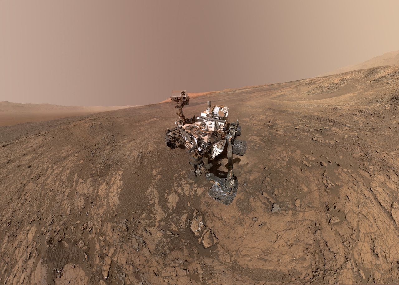 rover on martian surface with mountain in the background