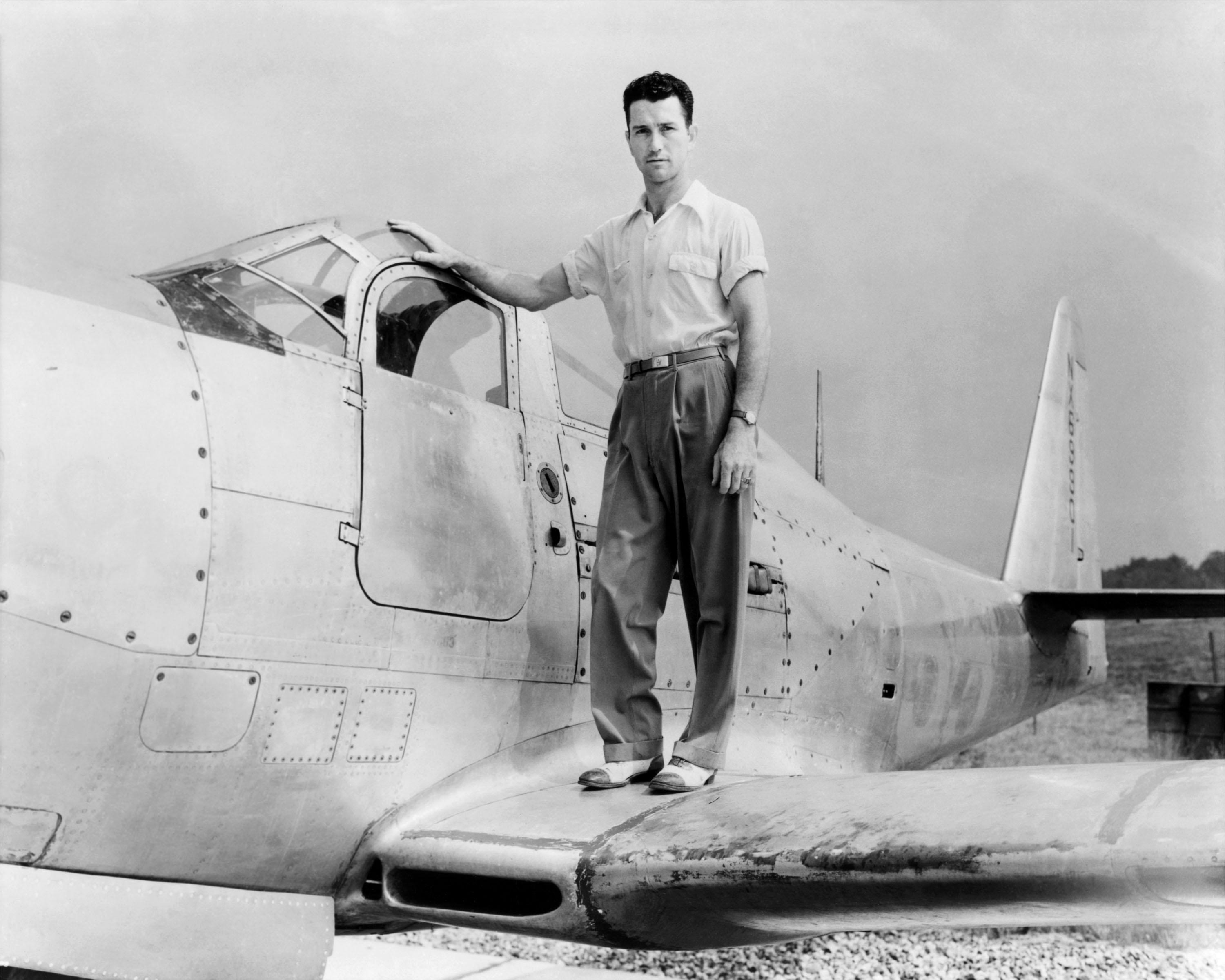 Black and white image of man standing on the wing of a plane.