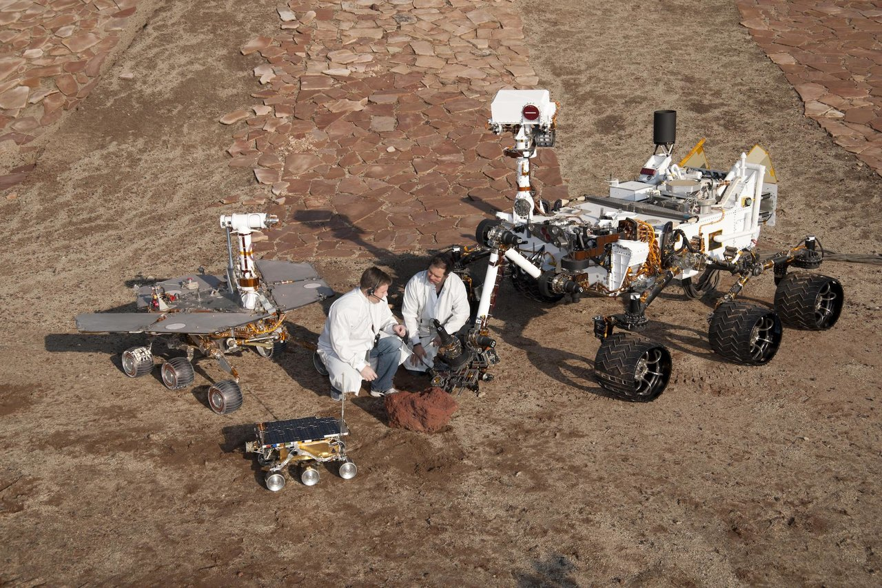 Two spacecraft engineers crouch next to rovers.