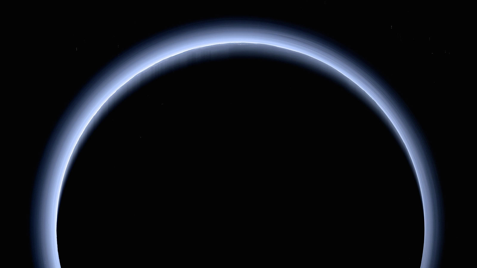 Crescent of Pluto as a blue haze over a dark orb.