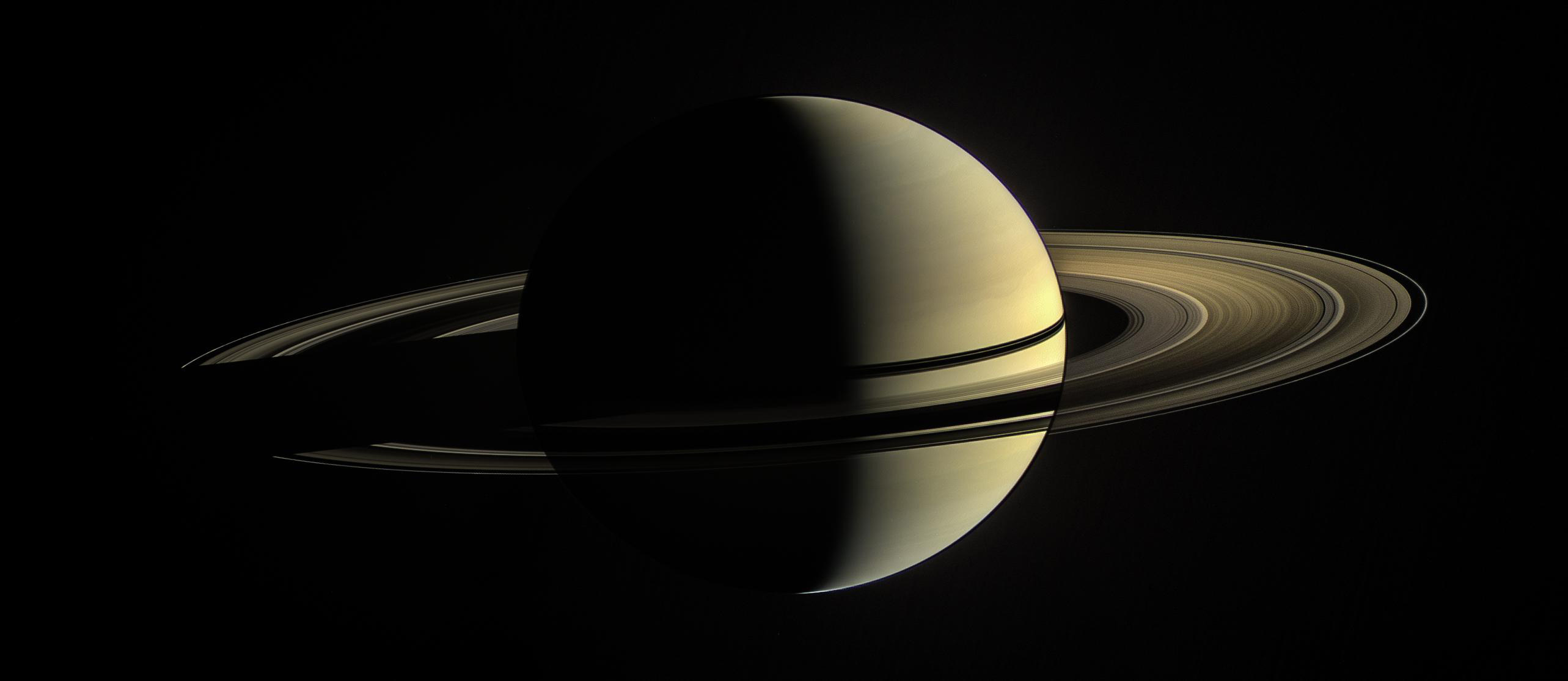 Full view of Saturn partially illuminated by the Sun.