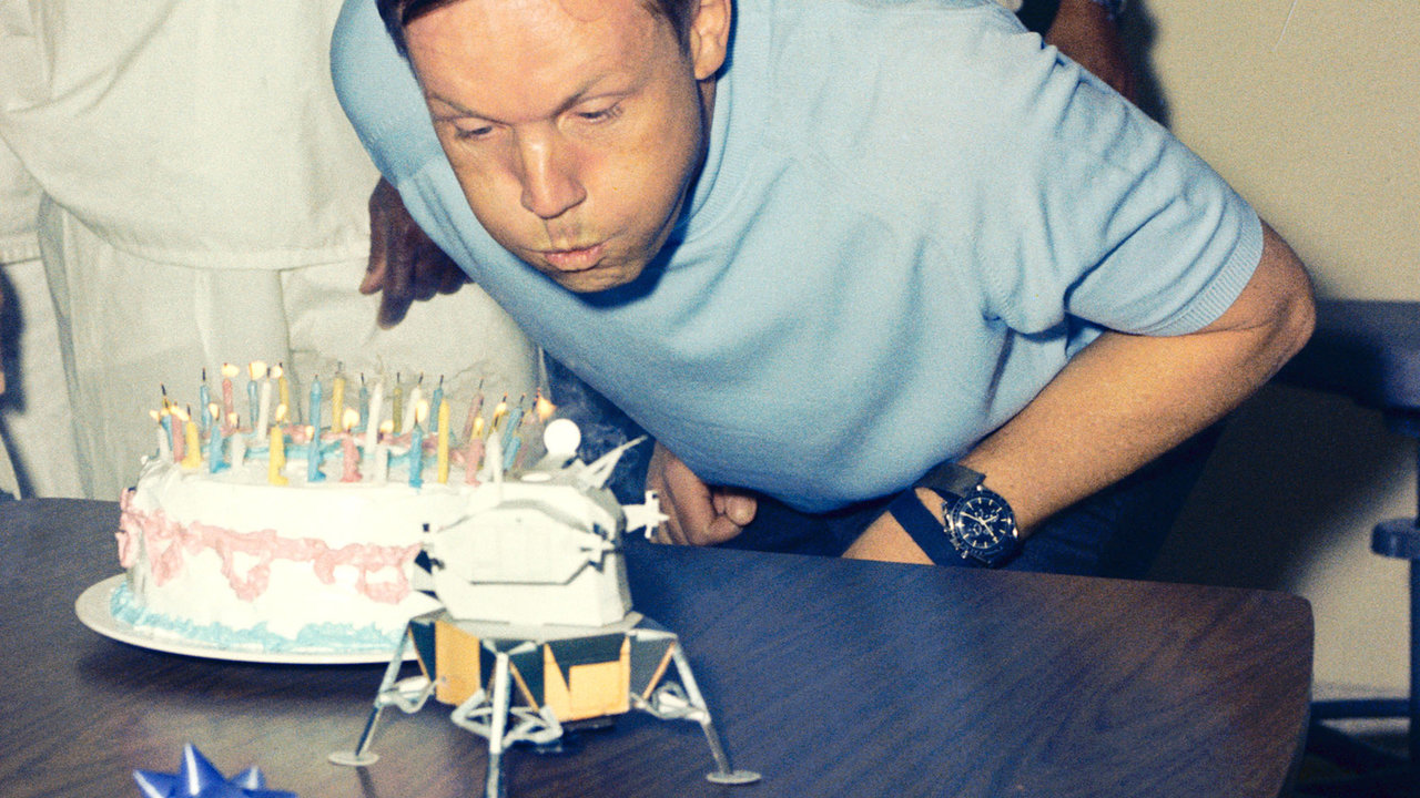 Neil Armstrong blowing out candles on a birthday cake.