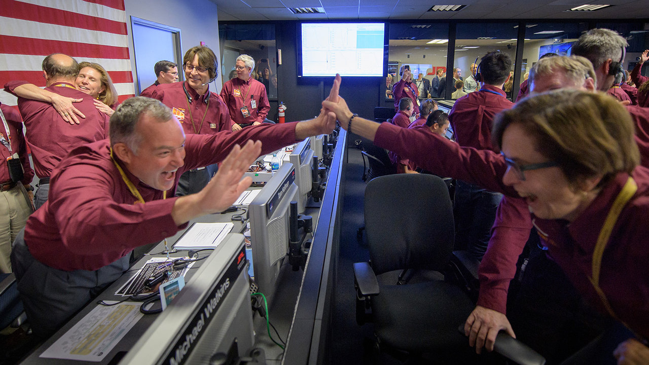 People cheering, high-fiving and hugging in mission control.