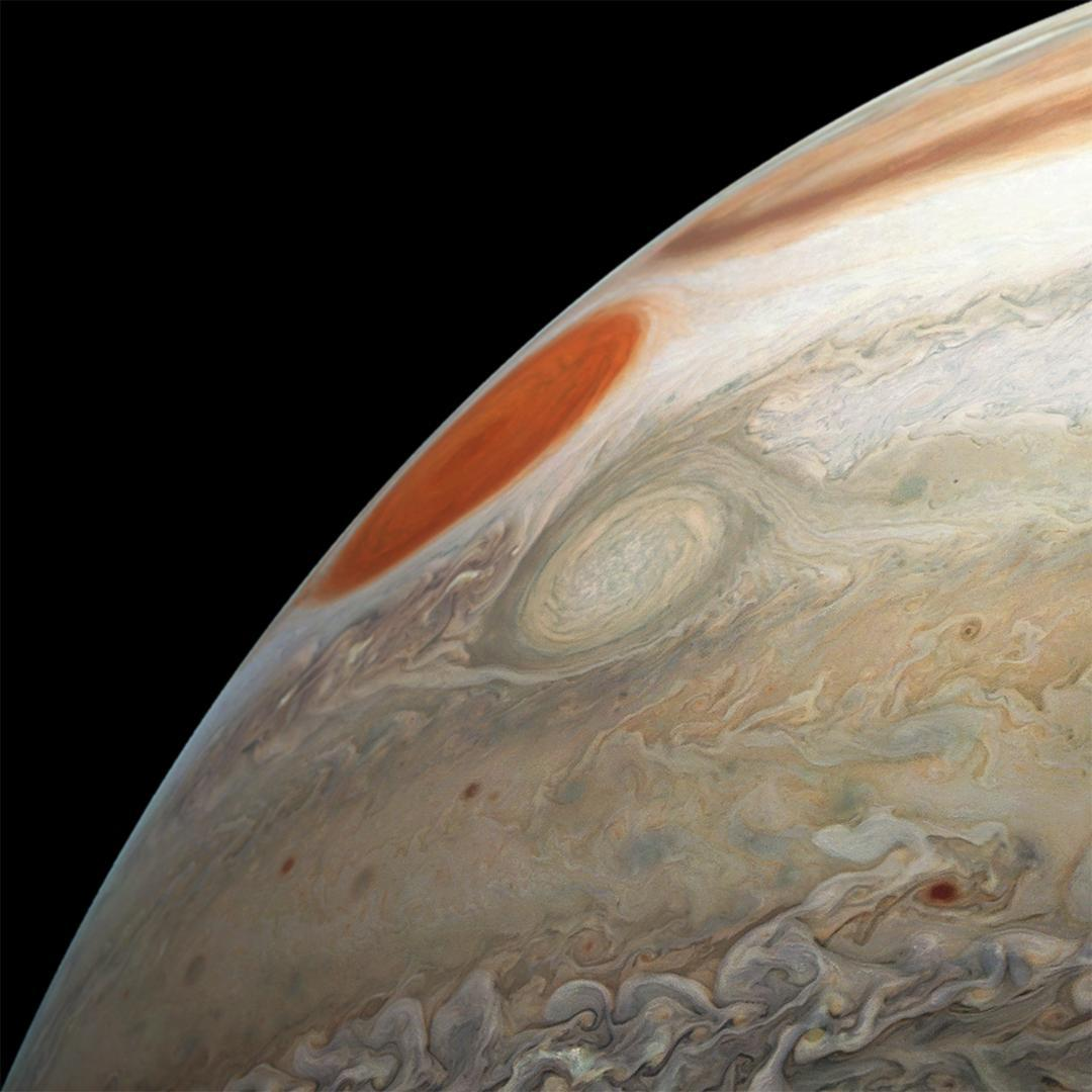 Limb of Jupiter with cloud swirls, oval storm and Great Red Spot.
