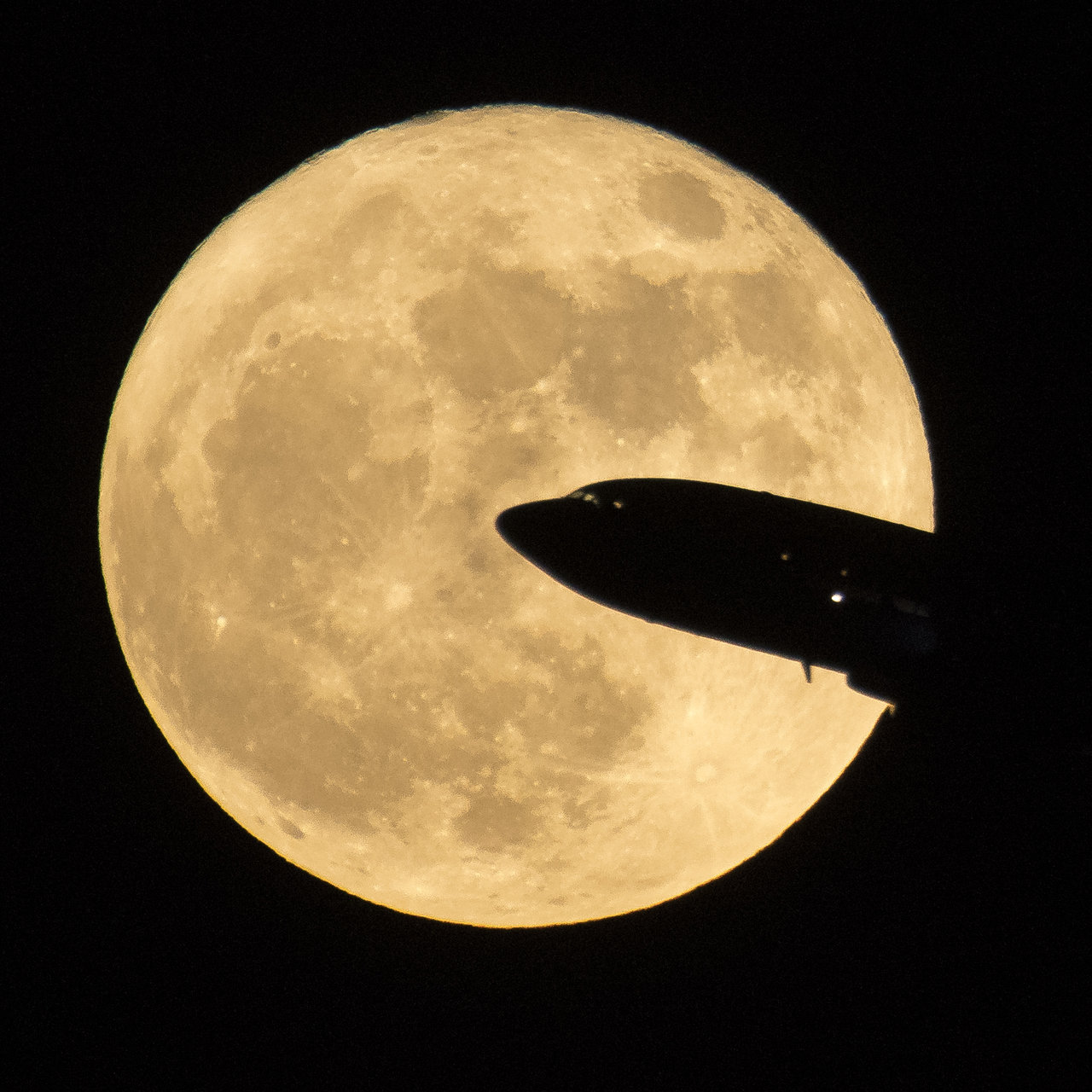 full moon with silhouette of airliner in foreground
