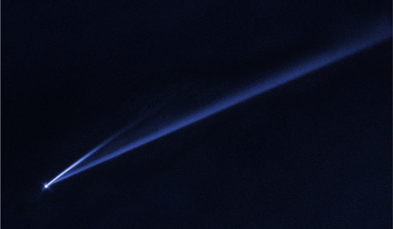 This Hubble Space Telescope image reveals the gradual self-destruction of an asteroid, whose ejected dusty material has formed two long, thin, comet-like tails. The longer tail stretches more than 500,000 miles (800,000 kilometers) and is roughly 3,000 miles (4,800 kilometers) wide. The shorter tail is about a quarter as long. The streamers will eventually disperse into space. Credit: NASA, ESA, K. Meech and J. Kleyna (University of Hawaii), and O. Hainaut (European Southern Observatory)