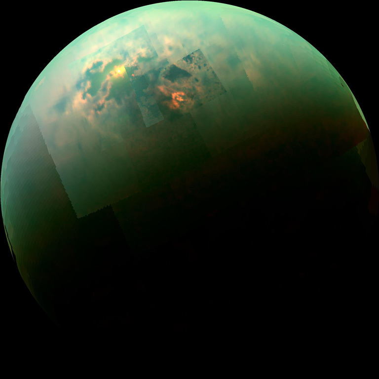 Global view of titan with sunlight glinting off seas and lakes.