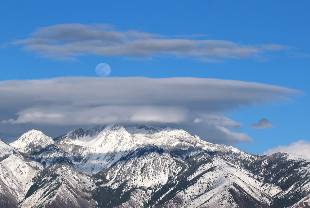 daylight moon over lenticular clouds and snowy mountaintops