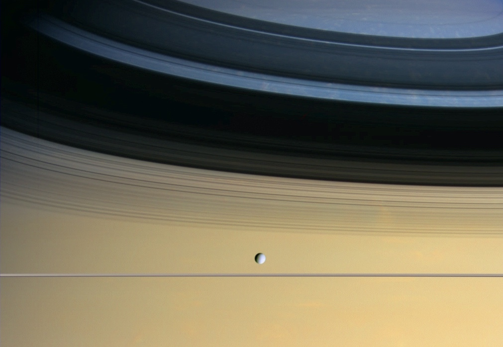 relatively tiny white moon floating before a colorful cloudscape on saturn