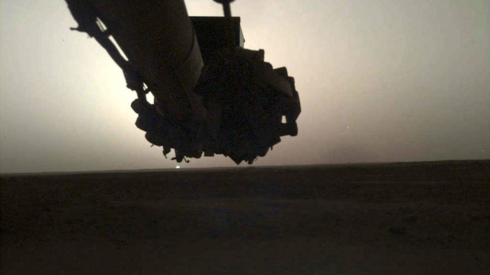 shadowed robotic arm above flat horizon with sun peeking over