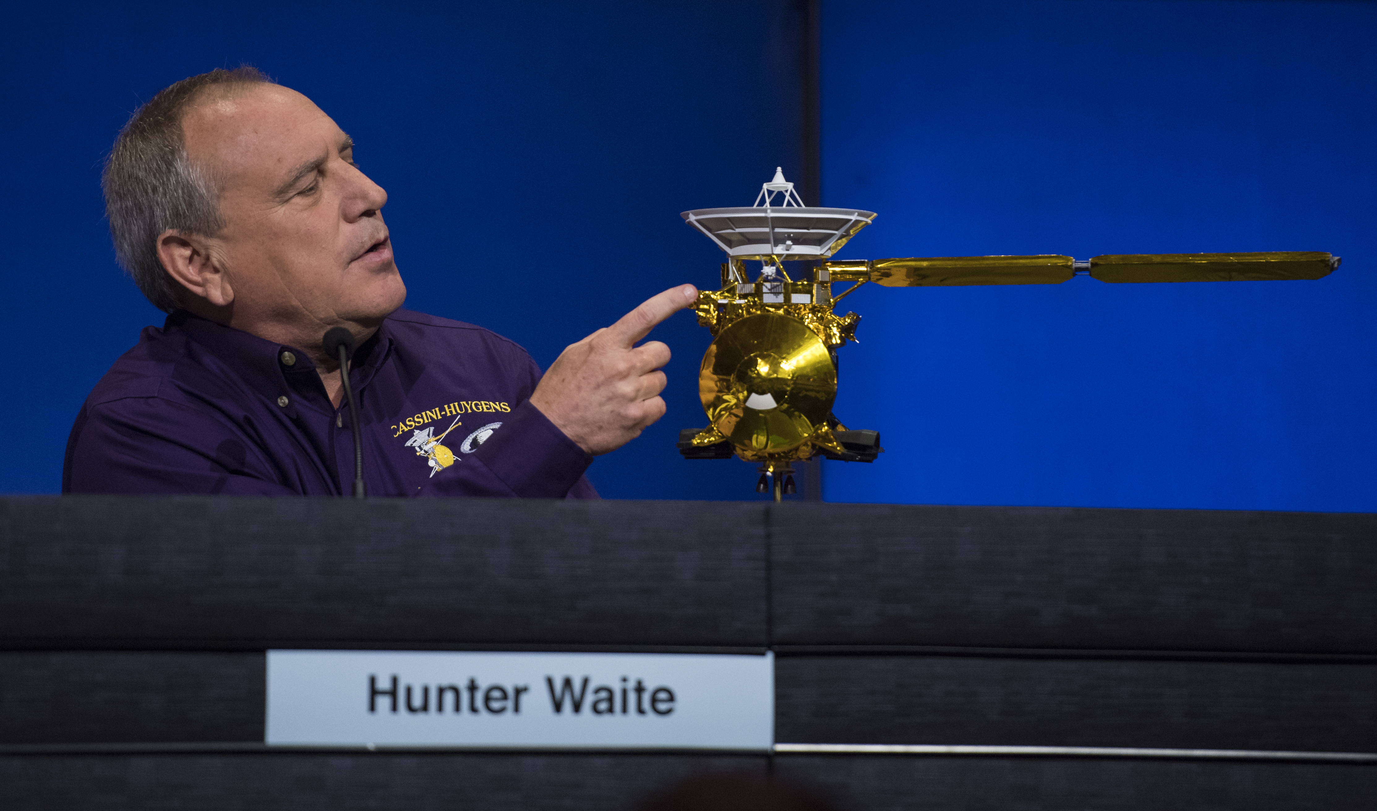 Man pointing at Cassini spacecraft model.