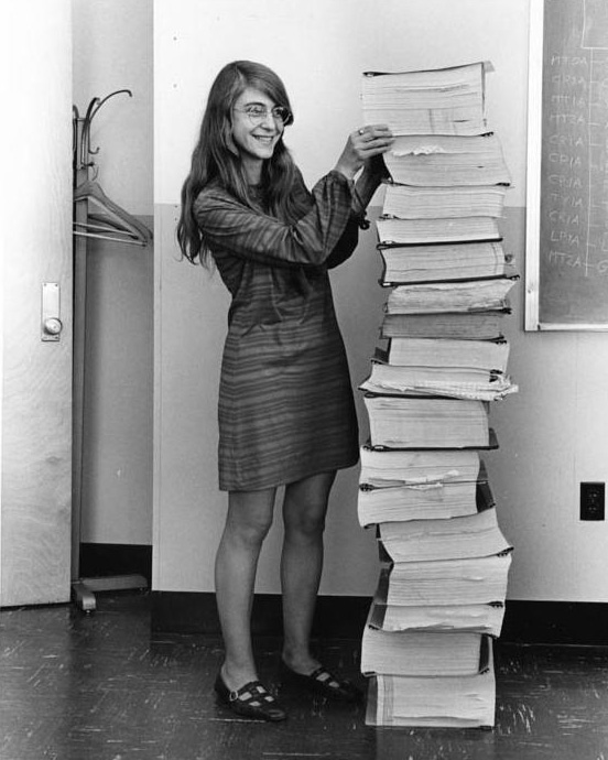 Smiling woman next to a huge printed stack of code that is as tall as she is.