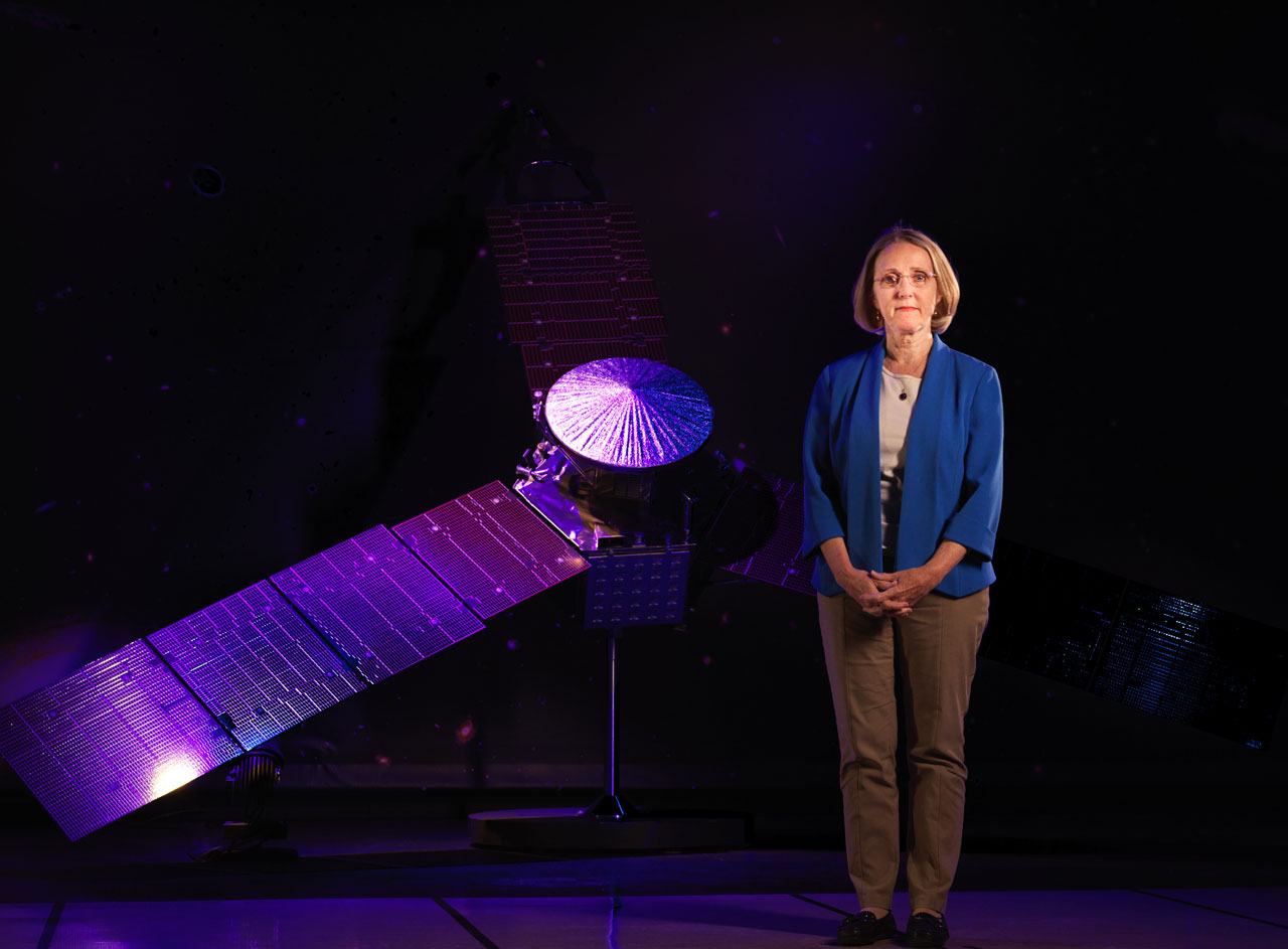 Woman standing next to spacecraft model.