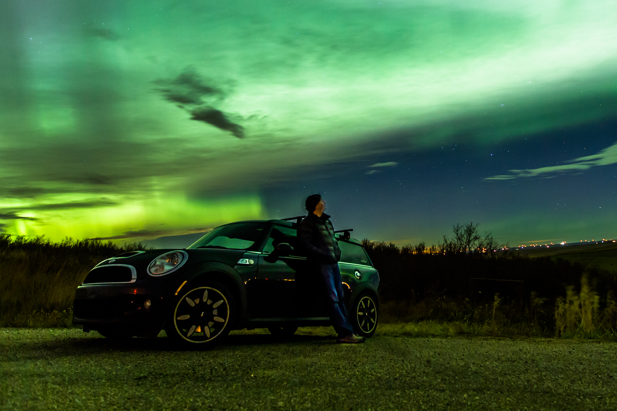Man leaning against a car with a bright, glowing green aurora filling the sky behind him.