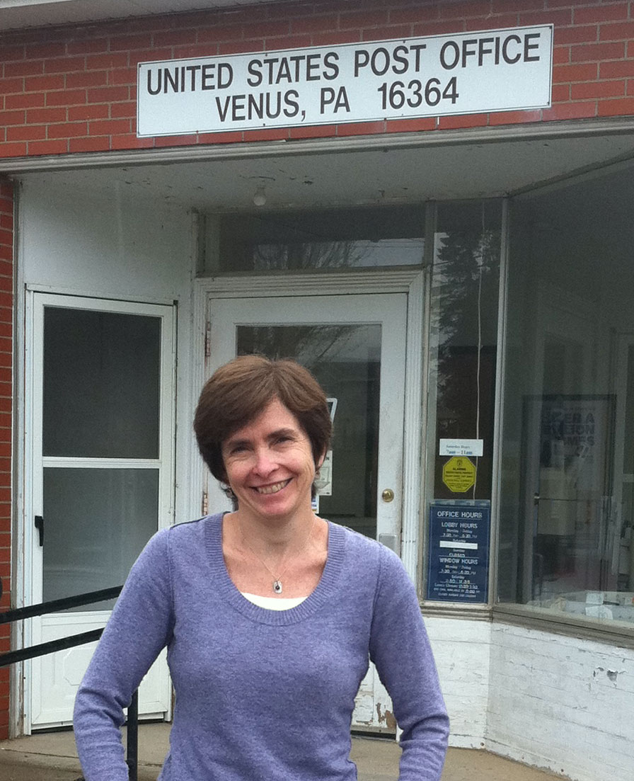 "Smiling woman standing in front of a Post Office. The sign says ""United States Post Office - Venus PA."""