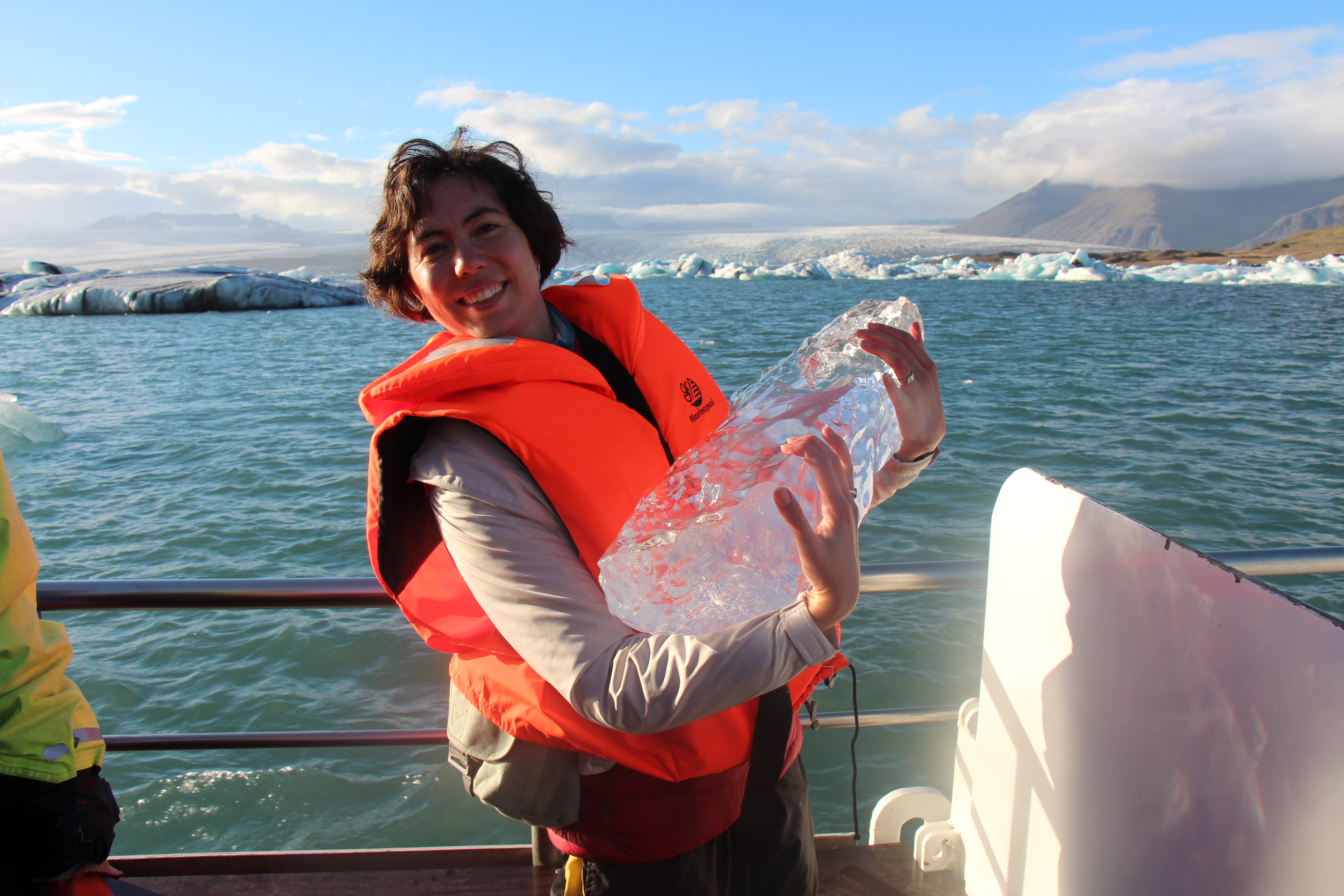 Smiling woman holding a block of ice on a boat.