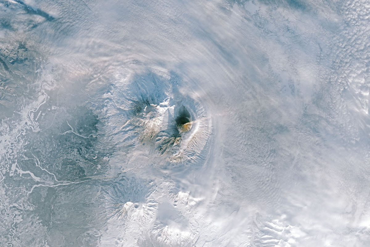 erupting volcanoes in snowy landscape seen from directly above