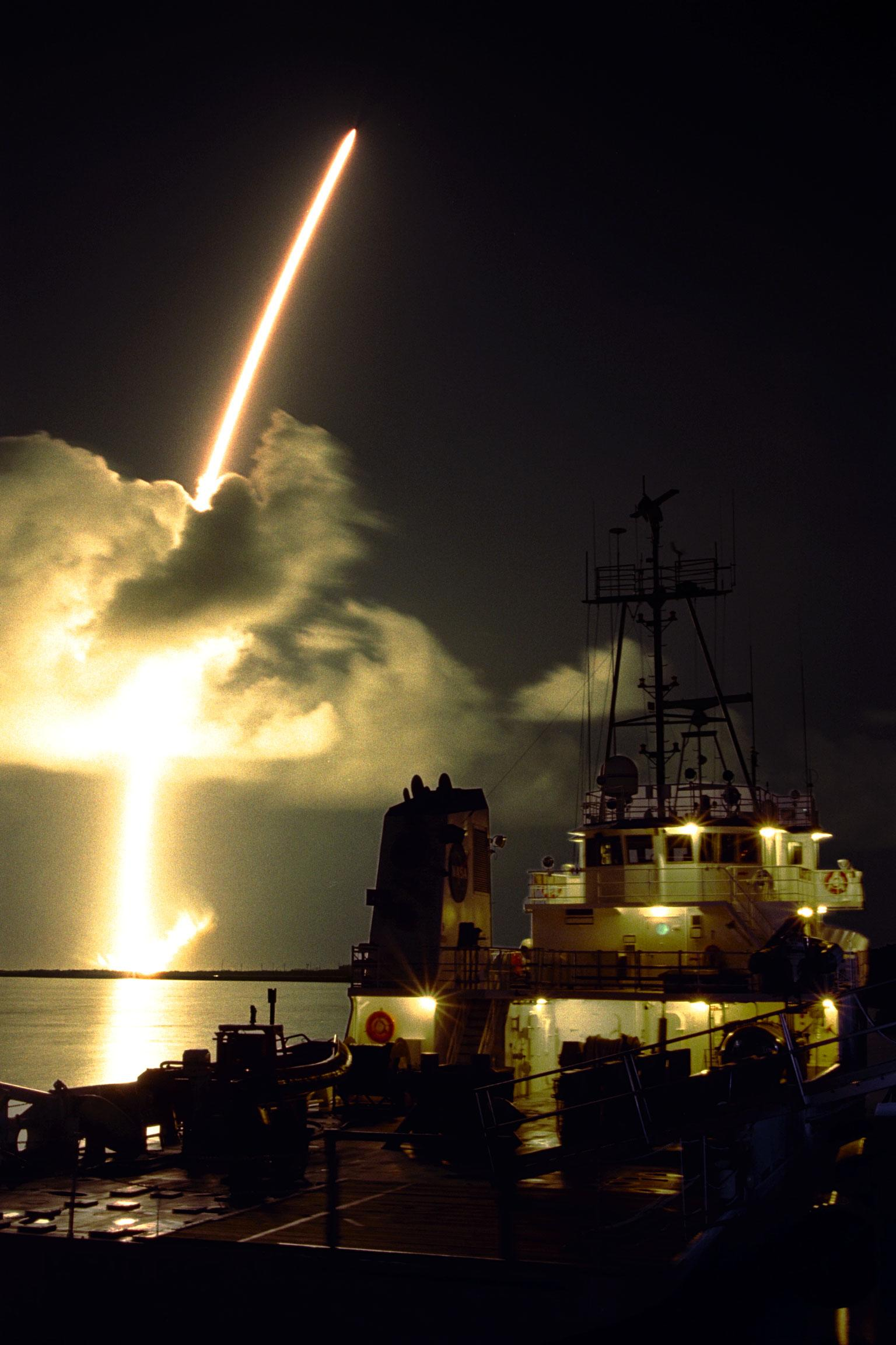 Color image of a rocket launch with a ship in the foreground.