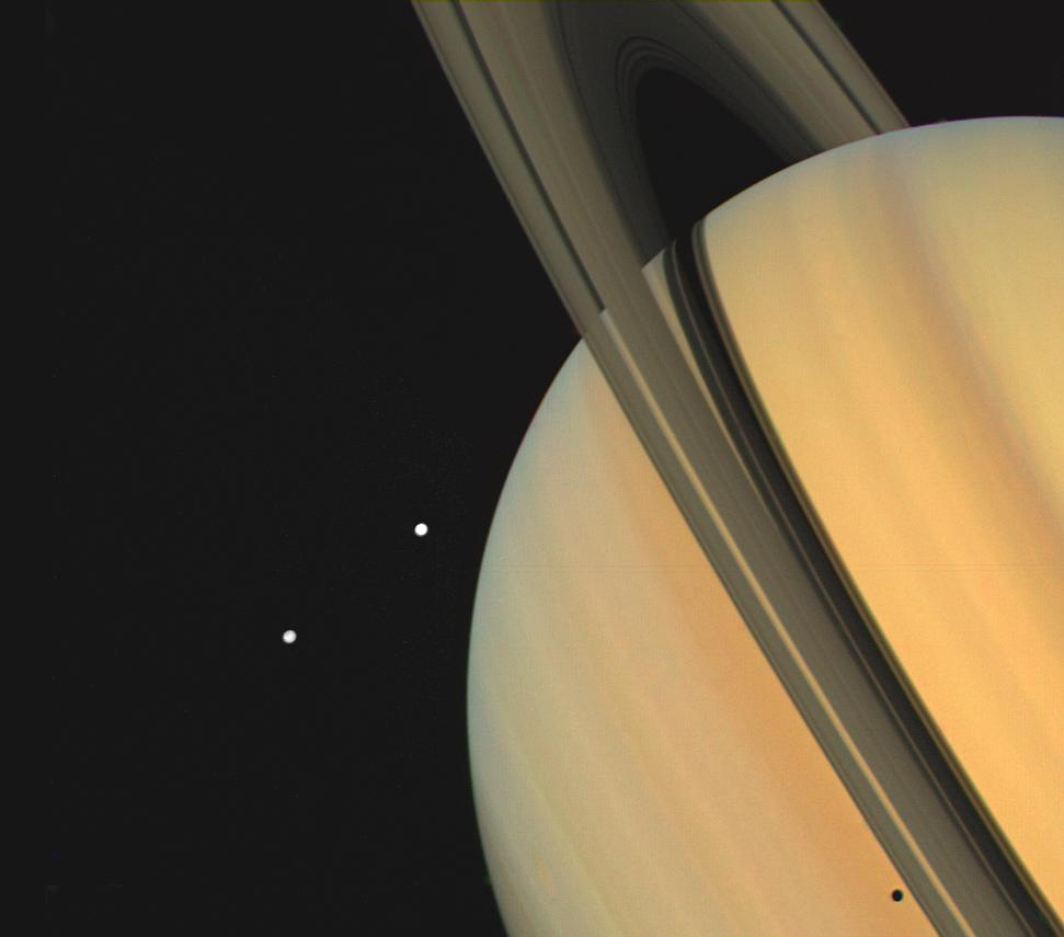 Color image of Saturn, its rings and two moons, Tethys and Dione.
