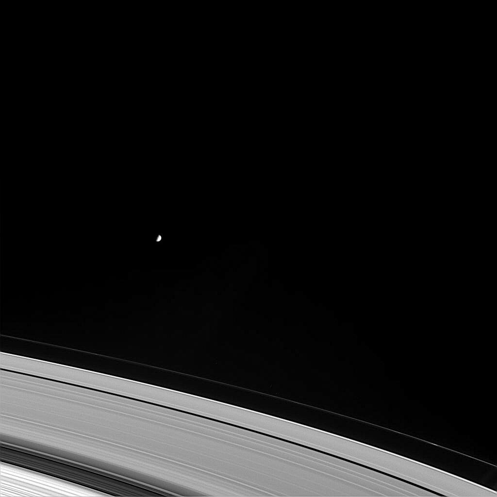 Black and white image of Mimas as a small white dot above the expanse of Saturn's rings.