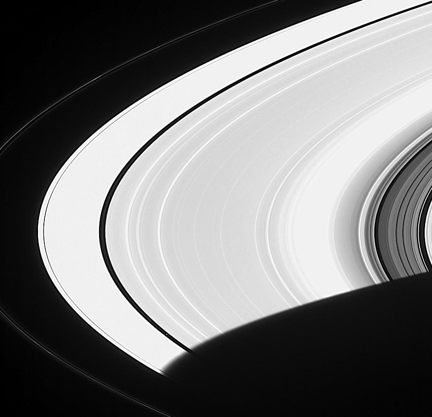 Pan is a faint speck in a gap in the wide expanse of Saturn's ring.