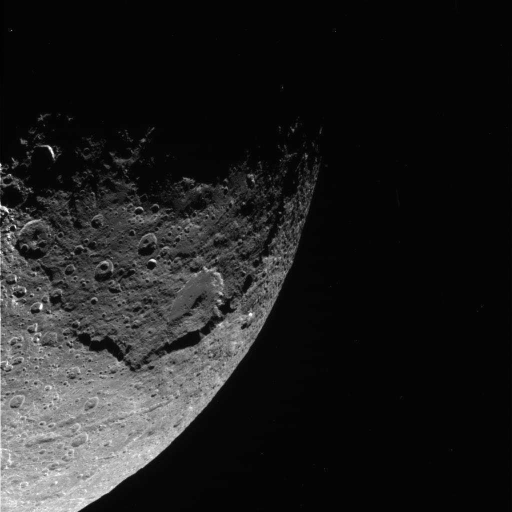 Black and white image showing a massive crater on Iapetus.