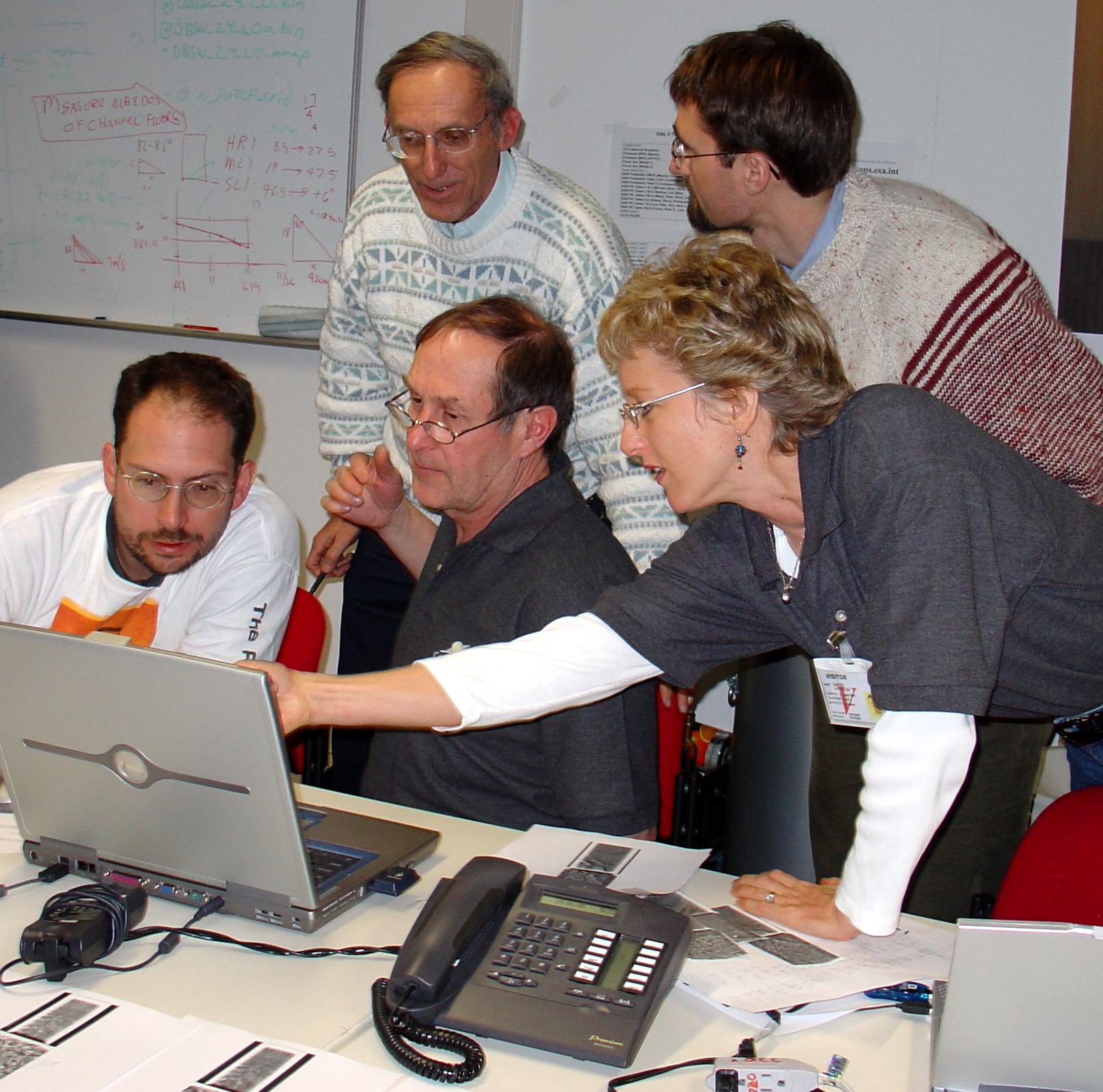 Five scientists gathered around a laptop looking at Huygens data
