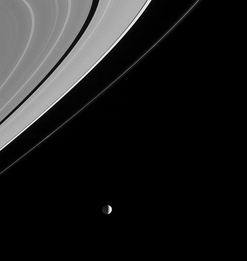 Black and white image of Mimas to the left of Saturn's rings.
