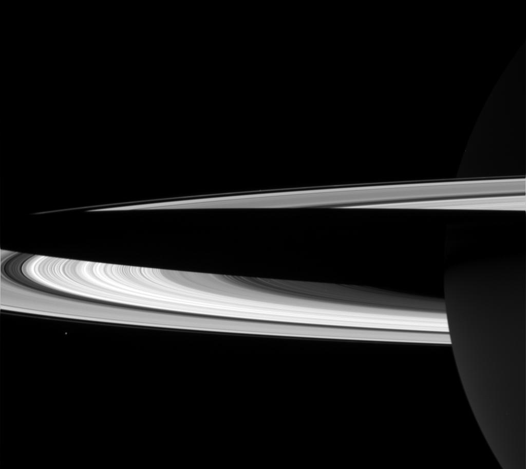 Shadow of Saturn falls across the rings in this black and white image. Tiny Janus hovers just below the rings.