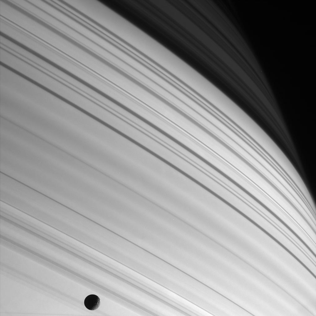 Black and white image of sharp bands of sunlight with the moon mimas in the lower half of the image.