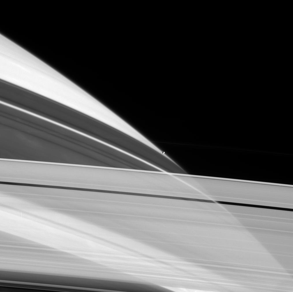 Cassini peers through the icy particles that comprise Saturn's rings as Prometheus sits perched on the planet's limb (edge).