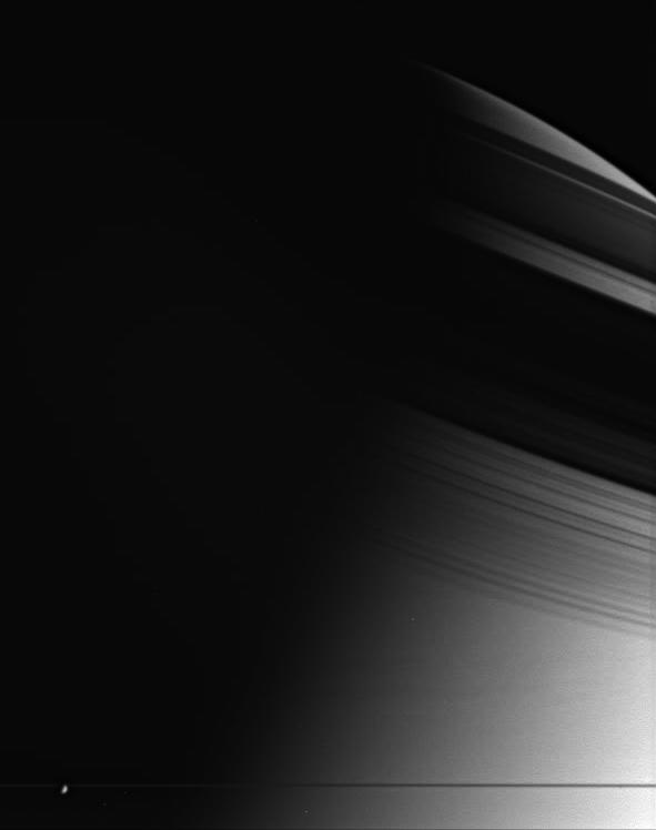The shadow of Saturn's rings on the atmosphere of Saturn. Enceladus is in the foreground