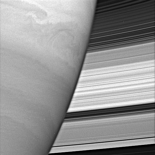 Turbulent swirls churn in Saturn's atmosphere while the planet's rings form a dazzling backdrop